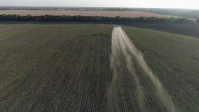El viejo avión de propulsor vuela sobre campo verde con trigo y hace el fertilizante que rocía en agrícola almacen de video
