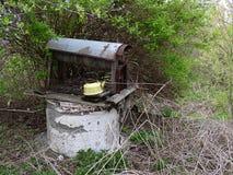 El viejo bien con una caldera en el jardín overgrown Foto de archivo libre de regalías