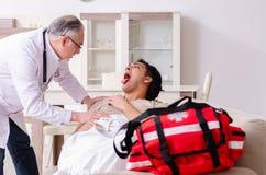 El viejo doctor de sexo masculino que visita al paciente masculino joven imagen de archivo libre de regalías