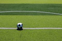 El viejo fútbol del fútbol en la línea blanca en el césped artificial Imágenes de archivo libres de regalías