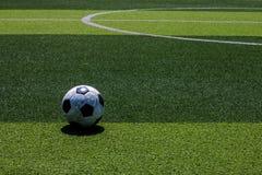 El viejo fútbol del fútbol en la línea blanca en el césped artificial Fotografía de archivo