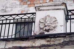 El viejo fragmento abandonado de la casa con la pintura pelada en la pared y el hierro echó fincing, flor que moldeaba por comple Imágenes de archivo libres de regalías