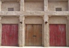 El viejo frente de la casa con tres coloreó puertas de madera imagen de archivo
