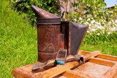 El viejo fumador y la otra herramienta del apicultor en la caja de madera Foto de archivo libre de regalías