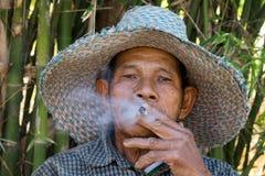 El viejo fumar asiático de los hombres Foto de archivo libre de regalías