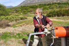 El viejo granjero regula el tubo de agua Imagenes de archivo