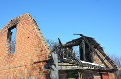 El viejo hogar quema abajo Daño de fuego del tejado de la casa del ladrillo Fotografía de archivo libre de regalías