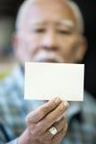 El viejo hombre asiático muestra su tarjeta de visita en blanco Fotografía de archivo