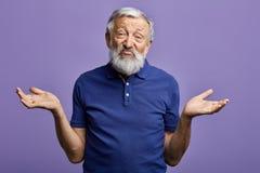 El viejo hombre barbudo expresa desorientado con los brazos aumentados que miran la cámara foto de archivo