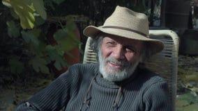 El viejo hombre blanco-cabelludo sabio que sonríe mirando el primer de la cámara metrajes