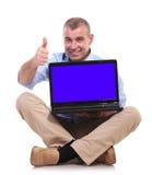 El viejo hombre casual sienta, lleva a cabo el ordenador portátil y la muestra aceptable Imagen de archivo libre de regalías