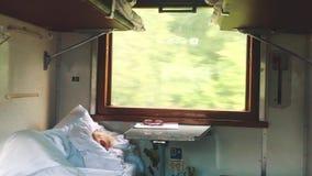 El viejo hombre está durmiendo en el tren E opinión ferroviaria del carro de la economía desde adentro almacen de metraje de vídeo