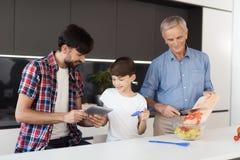 El viejo hombre está preparando una ensalada para la acción de gracias, hombre y un muchacho está mirando algo en una tableta del Fotos de archivo