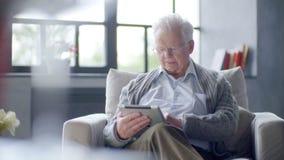 El viejo hombre está utilizando la tableta en casa metrajes