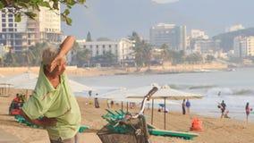 El viejo hombre hace ejercicios de la mañana en la playa en bici en Vietnam metrajes