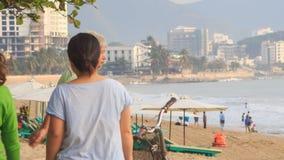 El viejo hombre hace ejercicios de la mañana en la playa en bici en Vietnam almacen de metraje de vídeo
