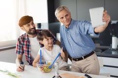 El viejo hombre hace un selfie con su hijo y nieto en la cocina, durante la preparación de una ensalada Imágenes de archivo libres de regalías