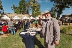 El viejo hombre inteligente en sombrero y traje de negocios aumenta un vidrio de vino y dice la tostada en festival de la calle Fotografía de archivo