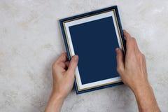 El viejo hombre intenta colgar un marco de madera azul con una fotografía Foto de archivo