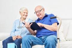 El viejo hombre lee el libro a su socio imagenes de archivo
