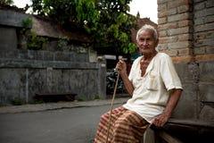 El viejo hombre local con el bastón de bambú se sienta en el banco de piedra imágenes de archivo libres de regalías
