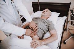 El viejo hombre miente en hospital El doctor Help Old Man imagenes de archivo