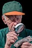 El viejo hombre mira a través - vidrio - de un billete de dólar que magnifica Imágenes de archivo libres de regalías