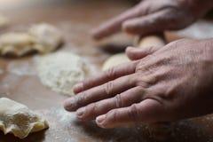 El viejo hombre rueda las manos crudas de la pasta Fotografía de archivo
