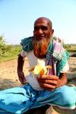 El viejo hombre se está sentando con el plátano Imagen de archivo libre de regalías