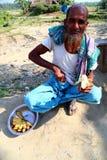 El viejo hombre se está sentando con el plátano Foto de archivo libre de regalías