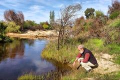 El viejo hombre se sienta al lado del río en montañas Foto de archivo libre de regalías