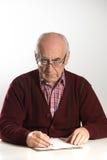 El viejo hombre trabaja con los documentos imagen de archivo libre de regalías