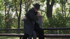 El viejo hombre viene a su señora y se sienta en sus rodillas de la manera humorística en el parque almacen de video