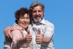 El viejo hombre y la mujer que hacen los pulgares suben gesto imagen de archivo