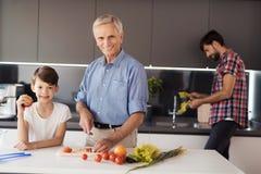 El viejo hombre y el muchacho están presentando en la cocina para hacer la ensalada El hombre detrás de ellos lavados que la lech Imágenes de archivo libres de regalías