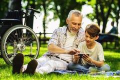 El viejo hombre y su nieto se están sentando en una comida campestre y están mirando algo en el smartphone Foto de archivo
