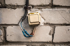 El viejo interruptor en la pared de ladrillo, torcida la cinta azul Fotografía de archivo