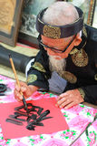 El viejo maestro con el papel rojo y la tinta negra Imagenes de archivo
