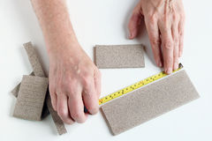 El viejo maestro mide el tamaño linear de las tejas de la loza Fotografía de archivo libre de regalías