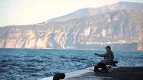 El viejo pescador coge un pescado en el mar almacen de metraje de vídeo