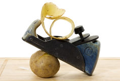 El viejo plano limpia las patatas. Foto de archivo libre de regalías