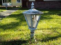 El viejo poste quebrado de la lámpara de calle del vintage se está colocando en la hierba verde fotos de archivo libres de regalías