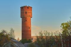 El viejo rojo se eleva torre de agua en la salida del sol o la puesta del sol Foto de archivo libre de regalías
