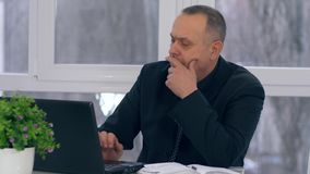El viejo trabajo del hombre de negocios con el ordenador portátil y toma notas en cuaderno en oficina metrajes
