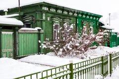 El viejo verde wodden la casa en día de invierno nublado en ciudad rusa antigua Imagen de archivo libre de regalías