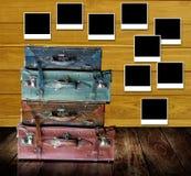 El viejo viaje empaqueta con los posts de los marcos de la foto en la pared de madera Imágenes de archivo libres de regalías