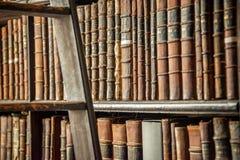 El viejo vintage reserva en el estante y la escalera de madera en una biblioteca Imágenes de archivo libres de regalías