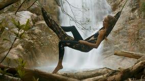 El viento descarga mentiras de la muchacha del espray de la cascada en hamaca