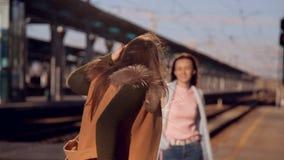 El viento descarga el sombrero de la muchacha Muchacha en un sombrero y vidrios en el ferrocarril que espera el tren almacen de metraje de vídeo