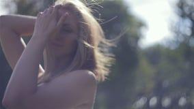 El viento infla a la muchacha feliz del pelo en campo almacen de video